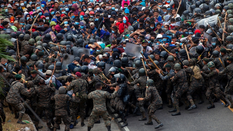 A large crowd of people are shown in conflict with security officials wearing military fatigues and helmets in a road.