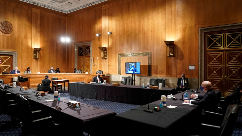 Homeland Security Secretary nominee Alejandro Mayorkas is shown seated at a long, cloth covered table in a largely empty room with tall, wooden walls.