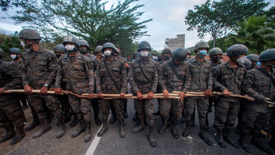 A line of security authorities are shown wearing fatigues and helmets and holding wooden poles.