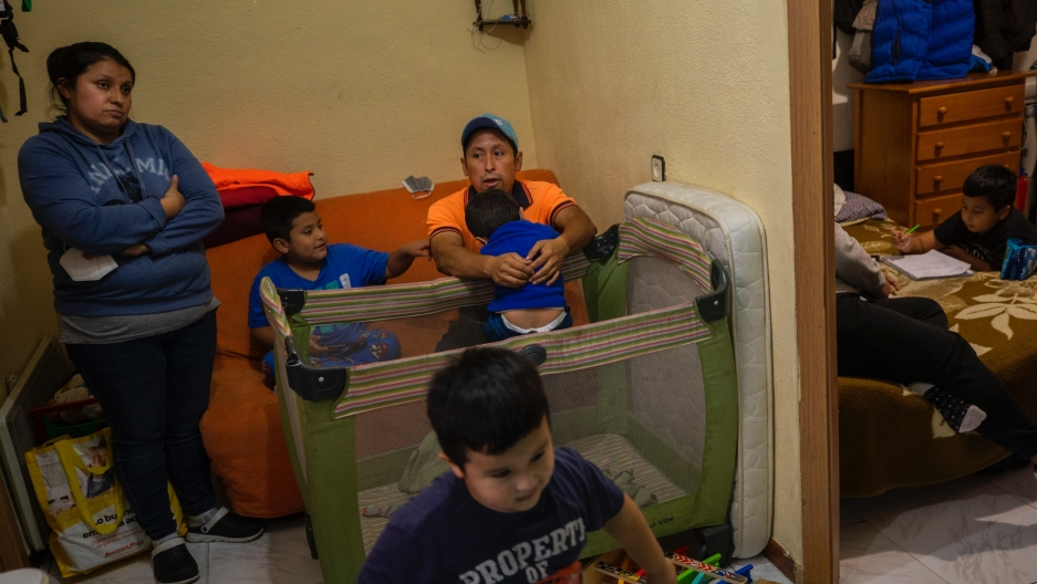 Erika Oliva, left, and her husband Benjamin Lopez's family gather inside their apartment in the southern neighborhood of Vallecas, in Madrid, Spain, Oct. 15, 2020.