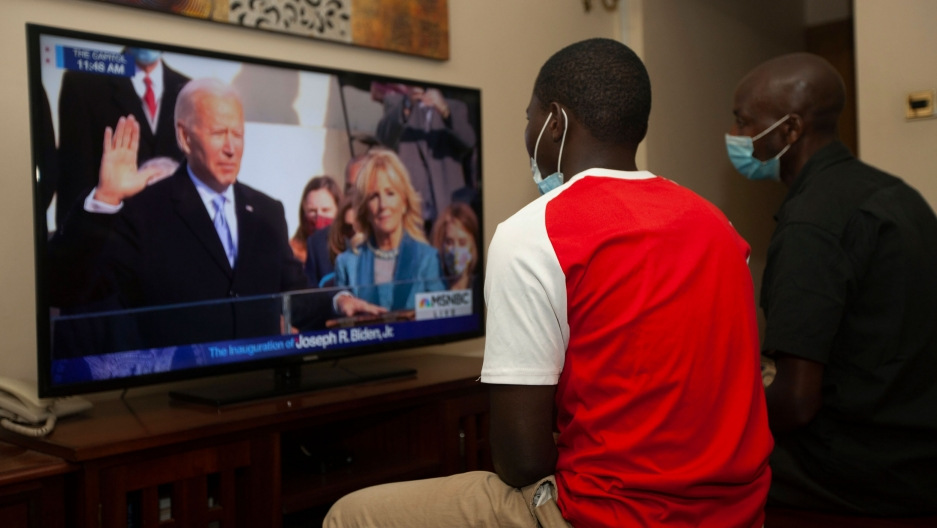 Two Kenyan men are shown sitting and watching President-elect Joe Biden's inauguration on TV.