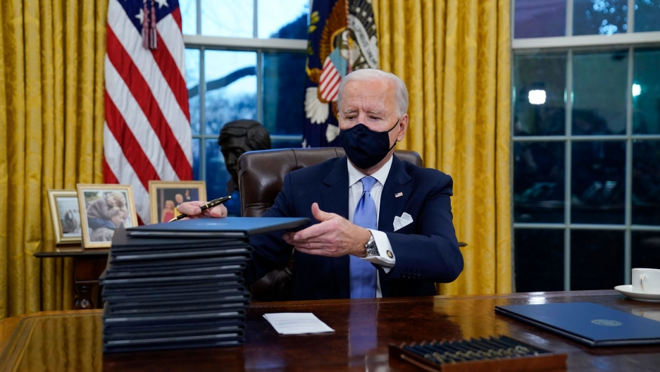 US President Joe Biden is shown seated at a wooden desk with a tall stack of embossed folders next to him.