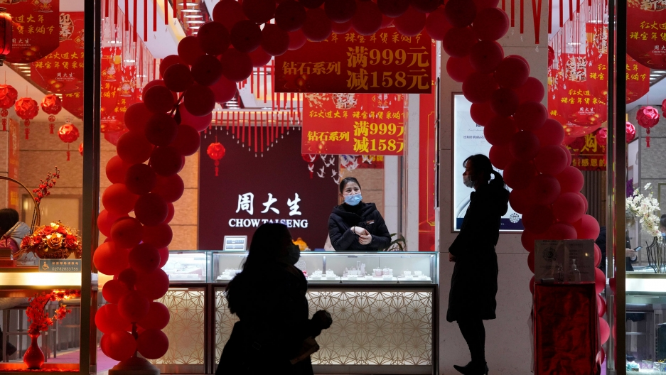 The the front window of jewelry store is shown framed by an arc of red balloons.
