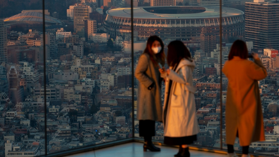 Japan National Stadium is shown in the distance from the vantage of a glass observatory where three women are standing.