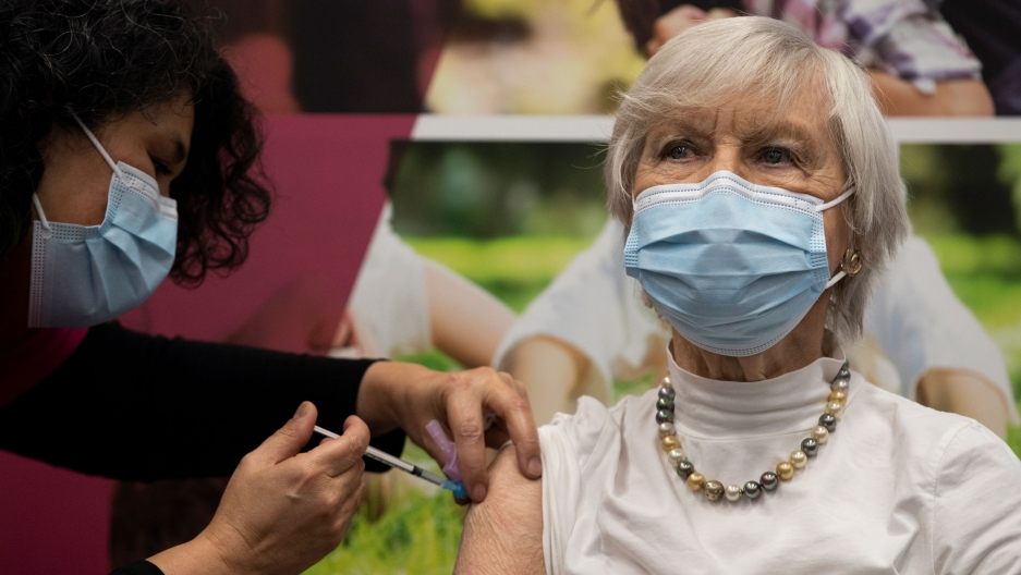 A woman is show wearing a white blouse with a pearl neclace and face mask while receiving a vaccine shot in her shoulder.