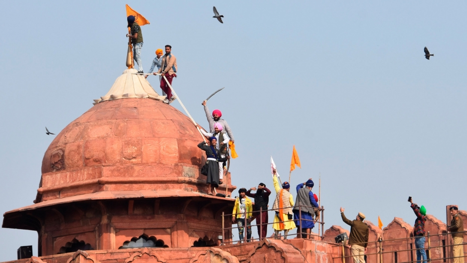 A group of men are shown on top of the redish-orange colored Red Fort monument with one man putting up an orange flag on top.