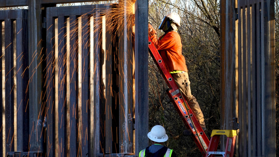 A man is shown standing on a ladder and using a machine causing sparks to fly in the construction of a border wall.