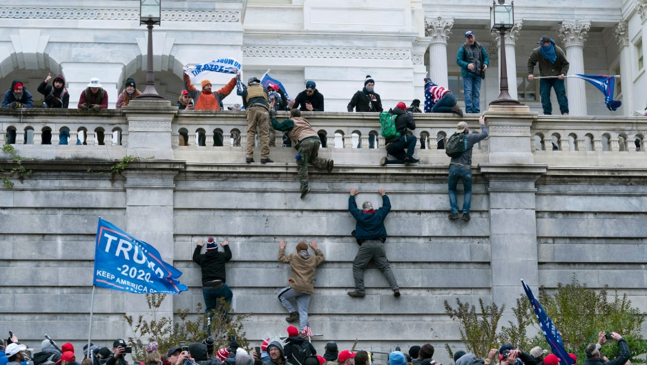 A large group of rioting supporters of former President Donald Trump are show carrying Trump 2020 flags and climbing the stone wall of the US Capitol.