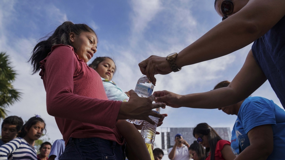"""n this Aug. 30, 2019, photo, migrants, most who were returned to Mexico under the Trump administration's """"Remain in Mexico"""" program, receive bottles of water given by volunteers in an encampment near the Gateway International Bridge in Matamoros, Mexico."""