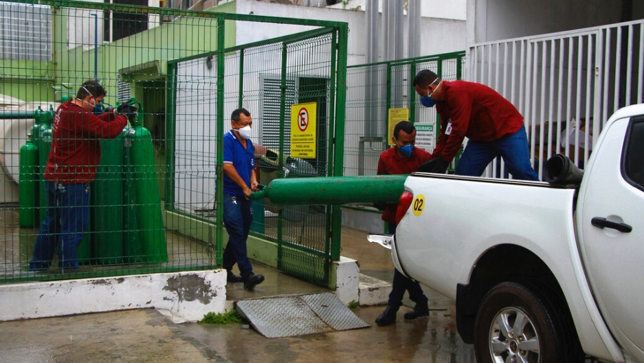 Amazonas Federal University's workers carry empty oxygen tanks at the Getulio Vargas Hospital amid the new coronavirus pandemic, Manaus, Brazil, Thursday, Jan. 14, 2021. Scores of COVID-19 patients in the Amazon rainforest's biggest city will be transferr