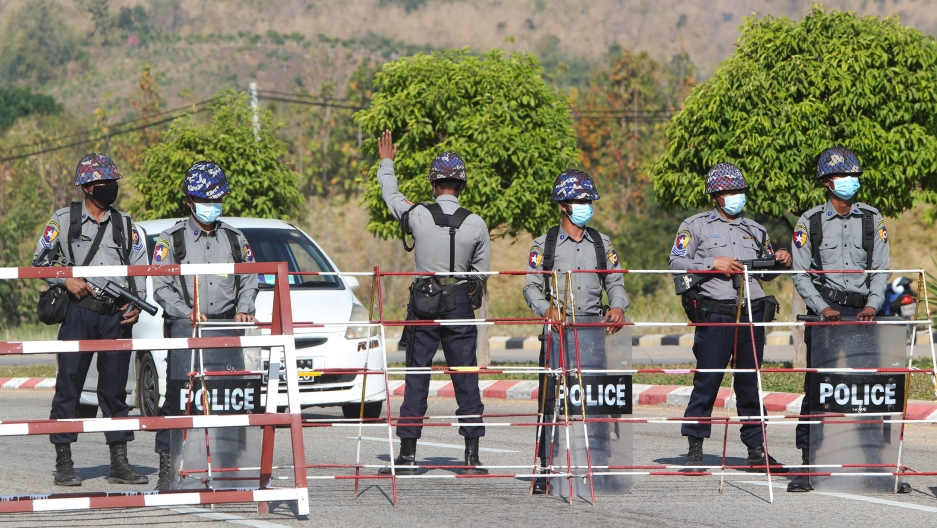 A line of six security authorities are shown standing next to a metal baracade blocking a road with one man holding his hand up stopping an approaching car.