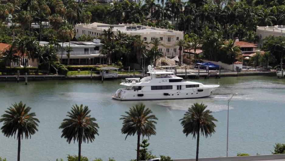 A yacht maneuvers near homes on Palm Island