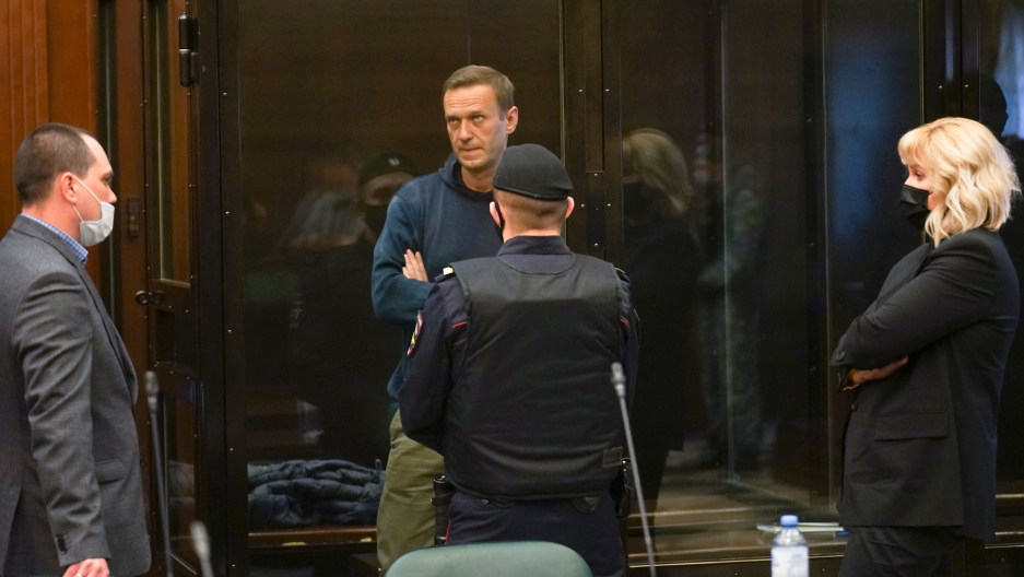 Alexei Navalny is shown standing inside of a clear glass cage in a courtroom with three people on the outside looking in on him.