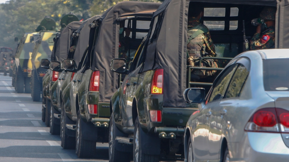 A long ling of military vehicles are shown painted in green-colored camoflage driving on a road.