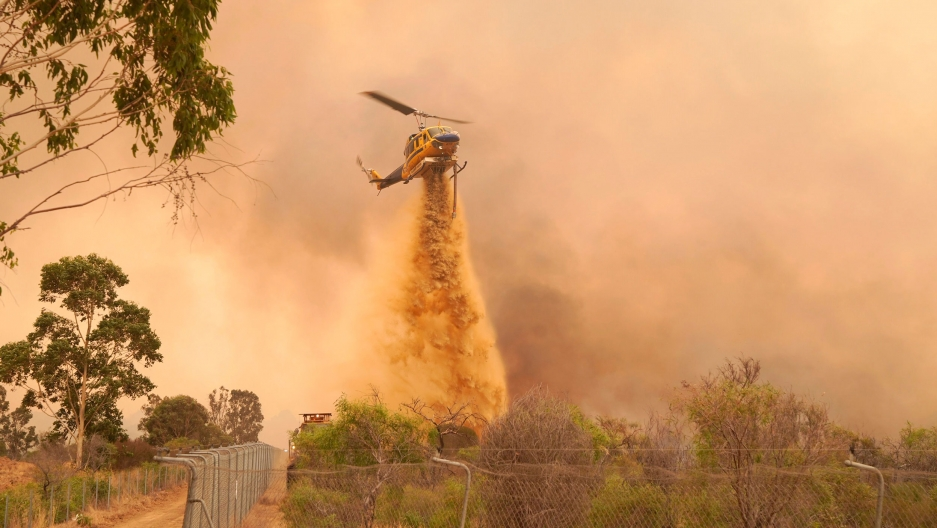 A helicopter is shown flying above a wooded area with a large metal fence on one side and dropping fire retardant.