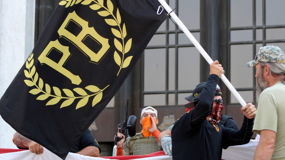 A man is shown wearing a face covering and holding a black flag with gold lettering with the letters P and B on it.
