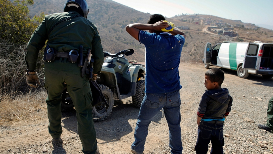 A man is shown with his hands behind his head as he is apprehended by a US border agent while a small boy is standing nearby.
