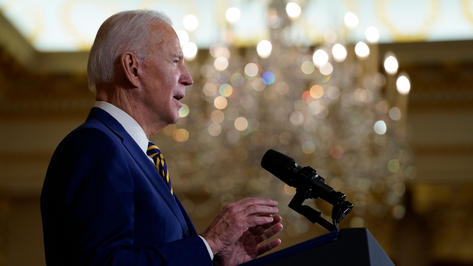 President Joe Biden is shown in profile speaking at a podium with microphones and wearing a blue suit.