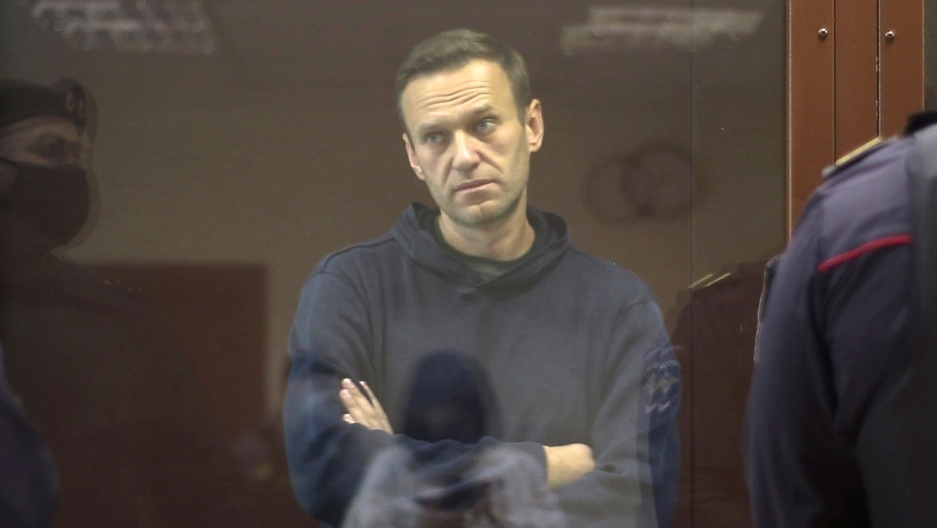 Alexei Navalny is shown wearing a blue hooded sweatshirt and standing with his arms folded in a glass cage in a Russian courtroom.