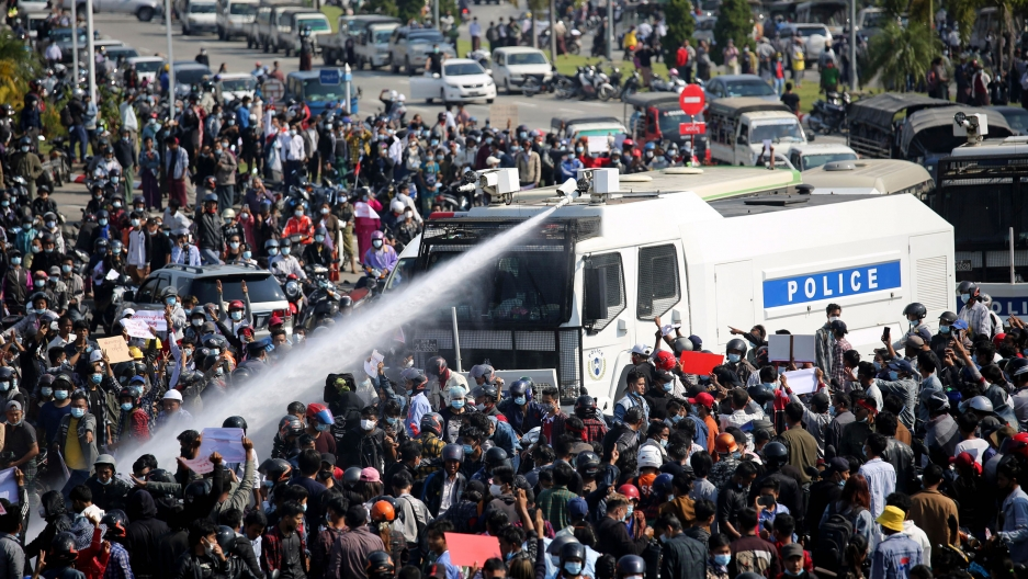 A large crowd of people are shown surrounding a police truck which is shooting a water cannon into the crowd.