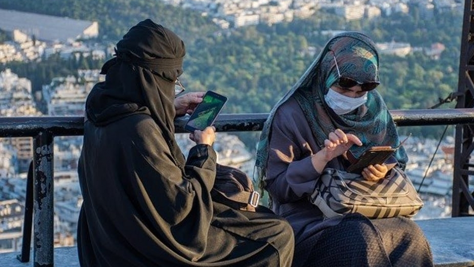 Two women sit outside, using their cell phones. They are wearing face masks in addition to head coverings.