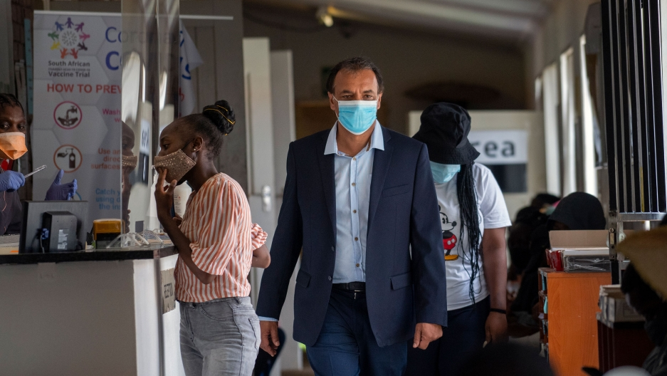 Professor Shabir Madhi is shown walking and wearing a blue face mask with a few people behind him also wearing face masks.