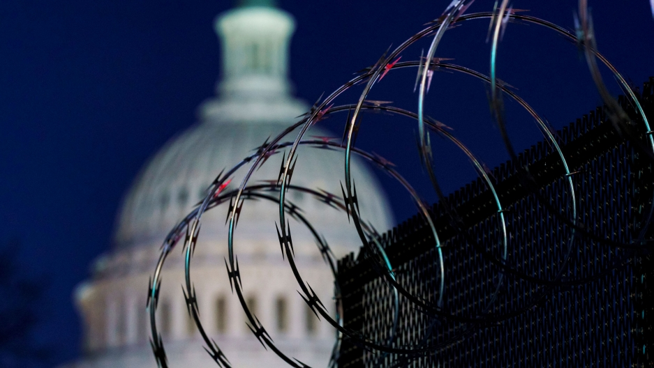 A fence with large rings of barbed wire is shown in the nearground with the dome of the US Capitol is soft focus in the background.