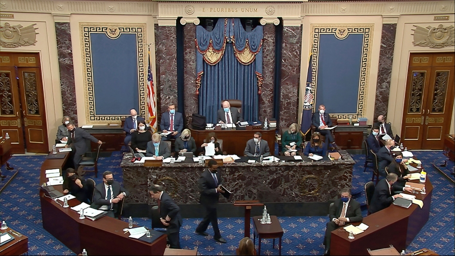 US lawmakers are shown gathering in the Senate with rounded wooden desks encircling a marble dais.