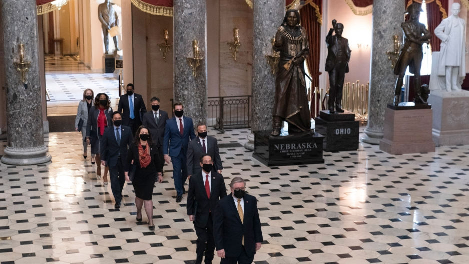 Two liines of lawmakers are shown walking across a black and white checkered floor in a large room with tall marble pillars.