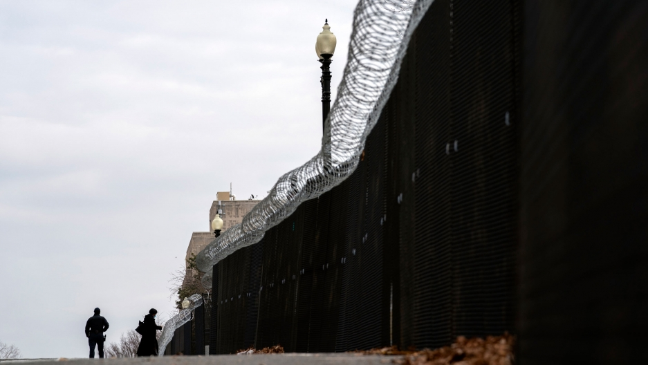 A tall fence is shown with barbed wire running along the top and a dark sheet obstructing the view through with two people shown in the distance.
