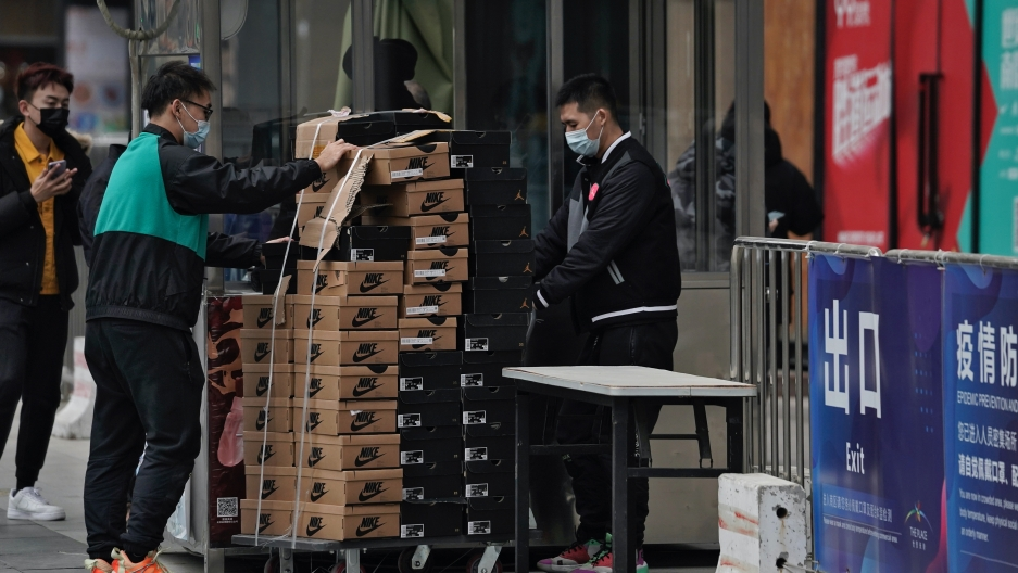 Workers wearing face masks to help curb the spread of the coronavirus push a cart loaded with shoes made by Nike past a security post at a shopping mall in Beijing, Jan. 14, 2021. China's exports rose in 2020 despite pressure from the coronavirus pandemic