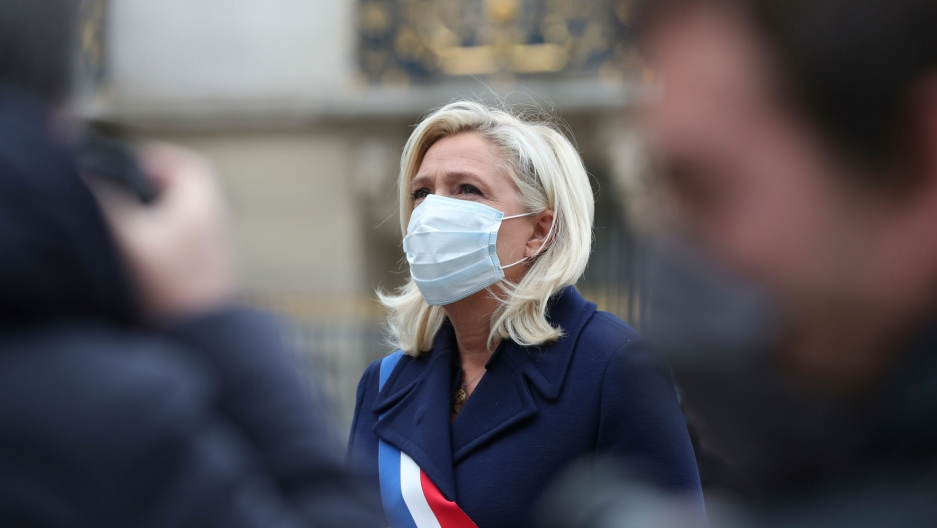 Marine Le Pen is shown wearing a blue jacket and a sash with the colors of the French flag over her shoulder.