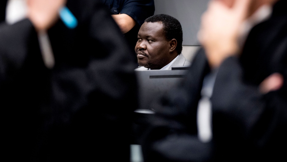 Patrice-Edouard Ngaïssona is seen only from the head up, blocked mostly by ICC judges standing in the nearground.