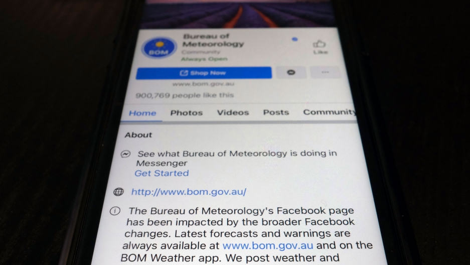 A close up photograph of a mobile phone showing the Bureau of Meteorology's page on the Facebook app.