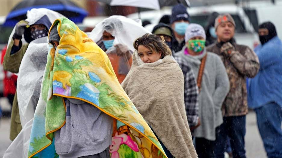 A line of people are shown with many people wrapping large blankets around themselves.