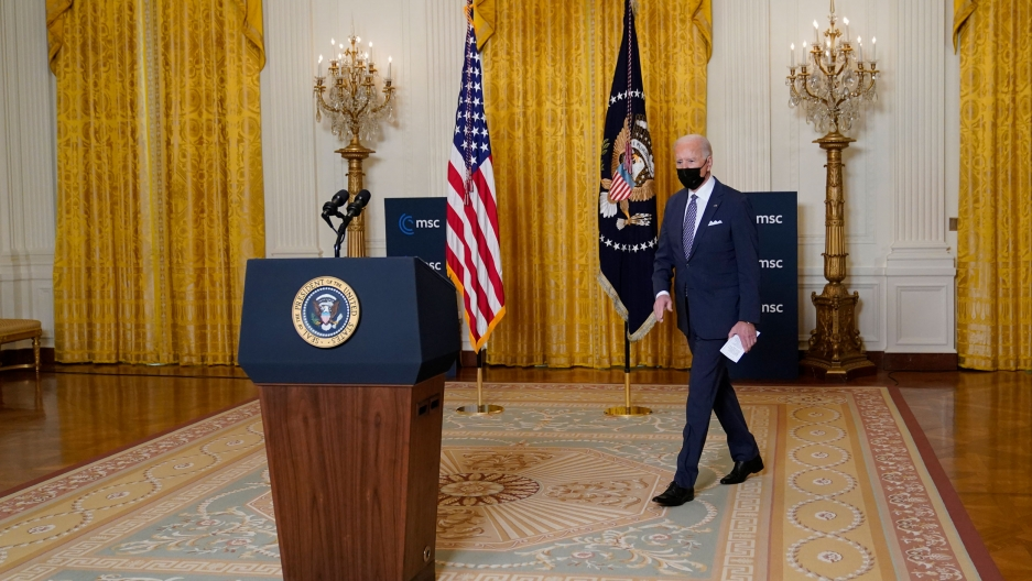 President Joe Biden is shown walking toward a podium with the White House crest on it and carrying a white piece of paper.