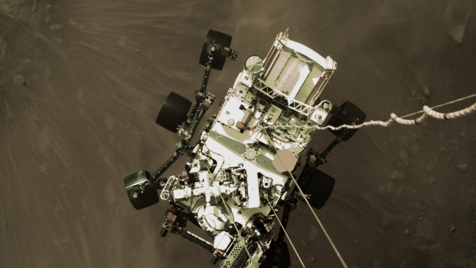 This Feb. 18, 2021, photo provided by NASA shows the Perseverance rover lowered toward the surface of Mars during its powered descent.