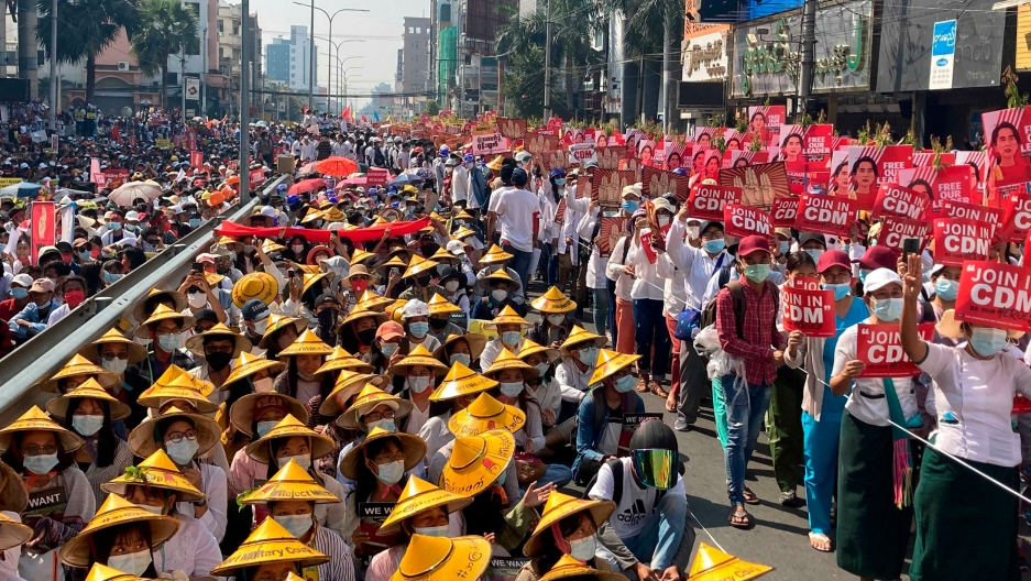 A large crowd of people are shown filling a street with many wearing traditional Asian hats and carrying red signs.