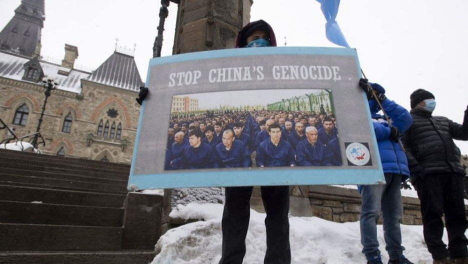 """A protester is shown holding a large sign the has the words, """"Stop China's Genocide"""" on it."""