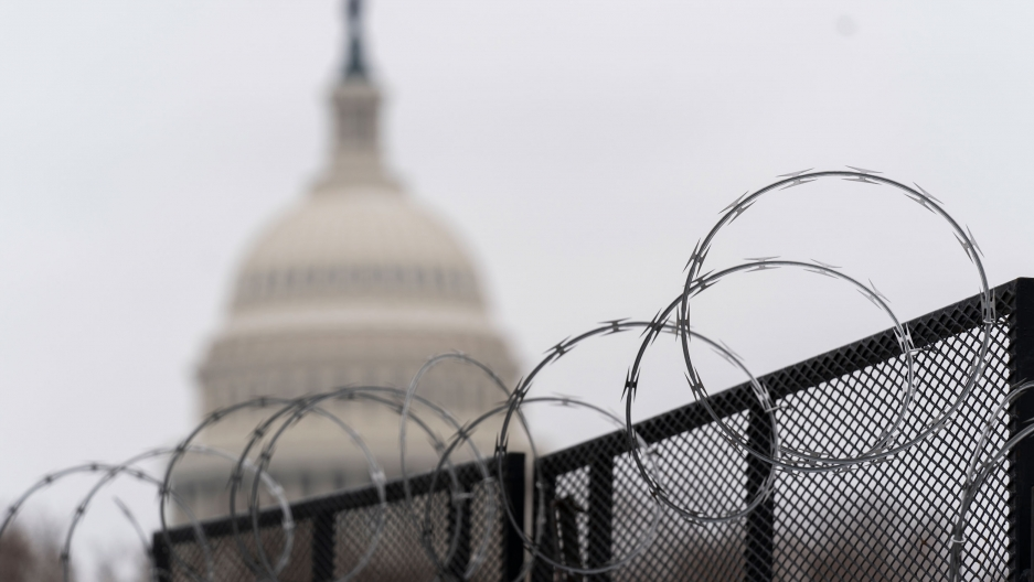 Circular razorwire is shown at the top of a fence with the dome of the US Capitol building in the distance and in soft focus.