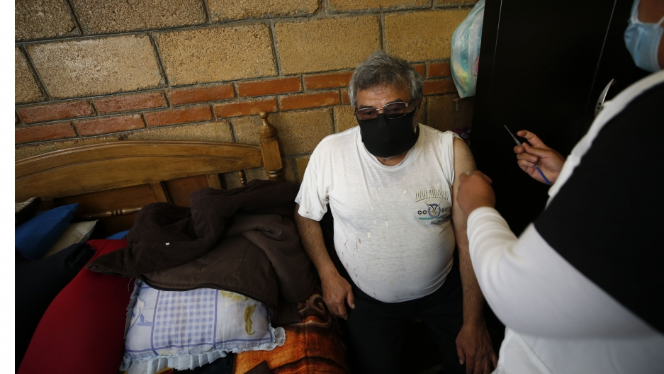 A nurse administers a shot to an elderly man wearing a white T-shirt and black pants at his home.