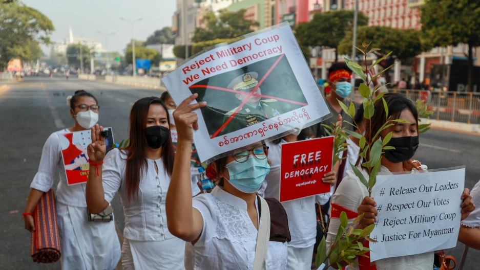 A demonstrator displays a picture of the defaced image of the commander in chief, Senior Gen. Min Aung Hlaing, also chairman of the State Administrative Council to protest against the military coup in Yangon, Myanmar, Feb. 17, 2021. The UN expert on human