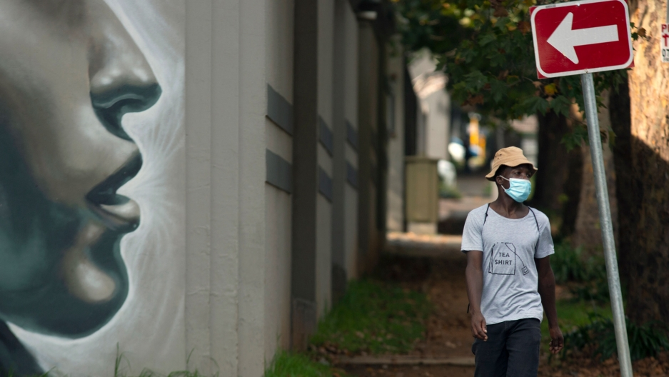 "A man is shown wearing a white t-shirt with ""tea shirt"" printed on it as he walks past large mural of a woman's face."