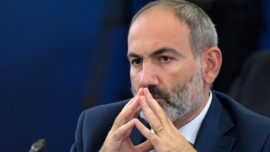 Armenian Prime Minister Nikol Pashinyan is shown with the fingertips of his hands pressed against each other and next to his mouth.