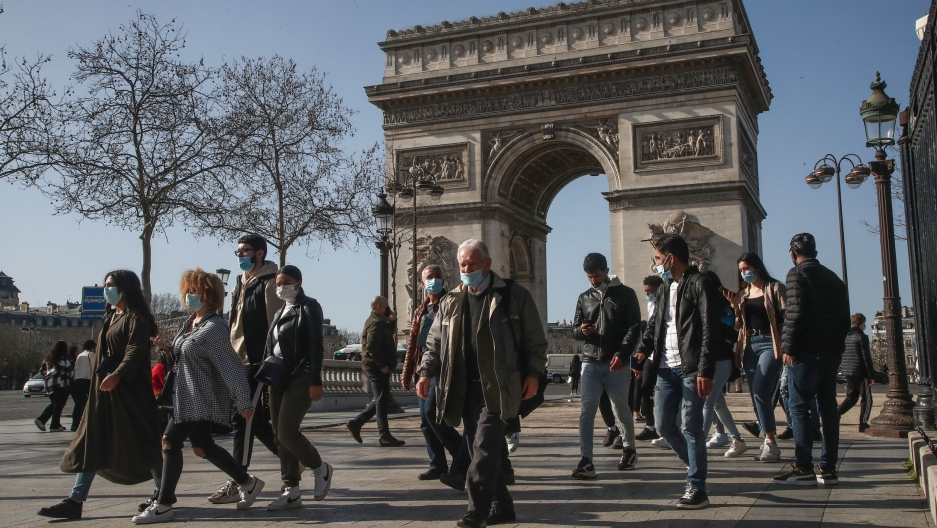 A crowd of people are shown walking with Paris' iconic Arc de Triomphe in the background.