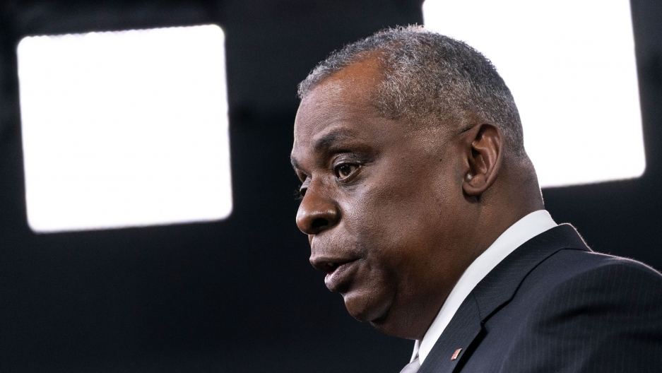 Secretary of Defense Lloyd Austin is shown in a close-up photograph from the side with bright white lights in the distance.