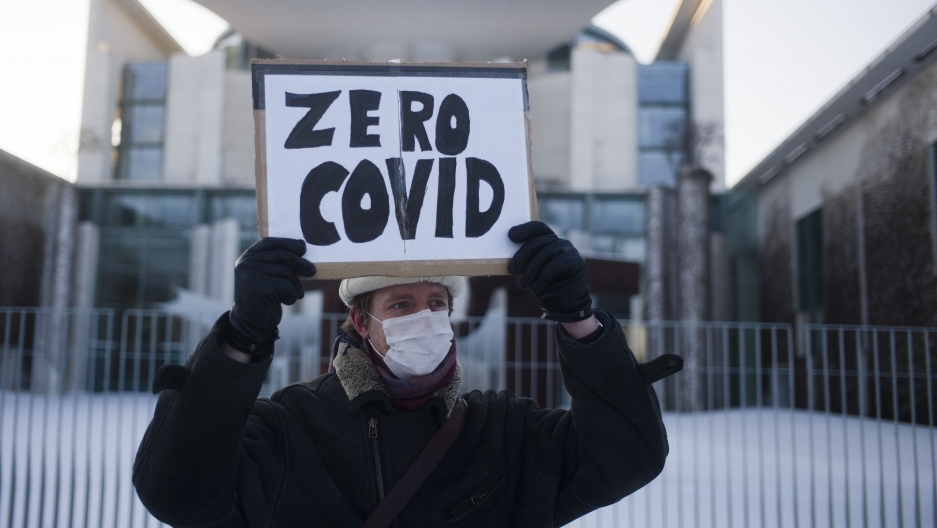 "A man holds a sign that says ""zero COVID"" wearing a winter jacket and hat outside in front of chancellery in Berlin."