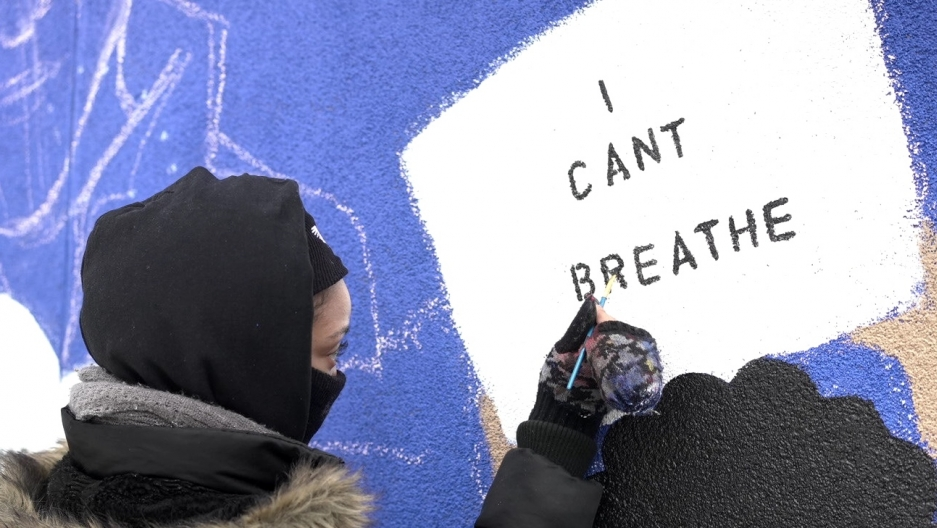 "A person paints a sign that says ""I can't breathe"" on a wall with a purple background."