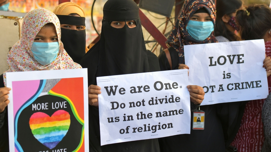 """Three women protestors hold up signs reading """"More Love, Less Hate""""; """"We are One. Do not divide us in the name of religion""""; and """"Love is not a crime."""""""