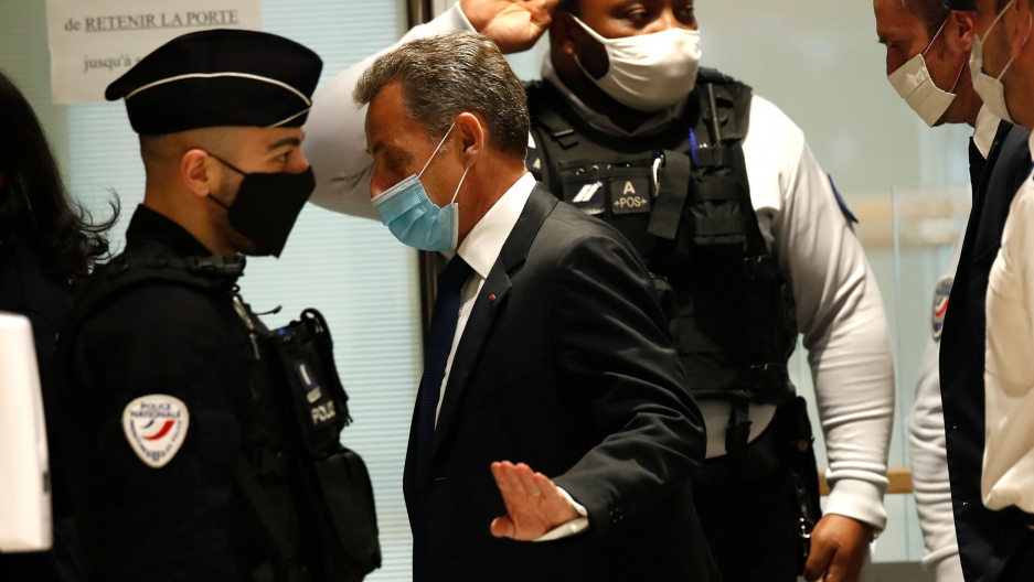Former French President Nicolas Sarkozy is shown wearing a dark suit and tie with a face mask, walking past security officials.